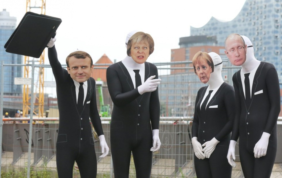 Aktivister utkledd som (f.h.) Frankrikes president Emmanuel Macron, Storbritannias statsminister Theresa May, Tysklands kansler Angela Merkel og Russlands president Vladimir Putin tar del i et opptrinn organisert av aktivistgruppen Attac. Scanpix/EPA.